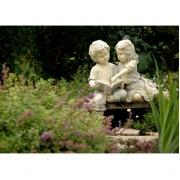 Beeld van lezende kinderen in een tuin